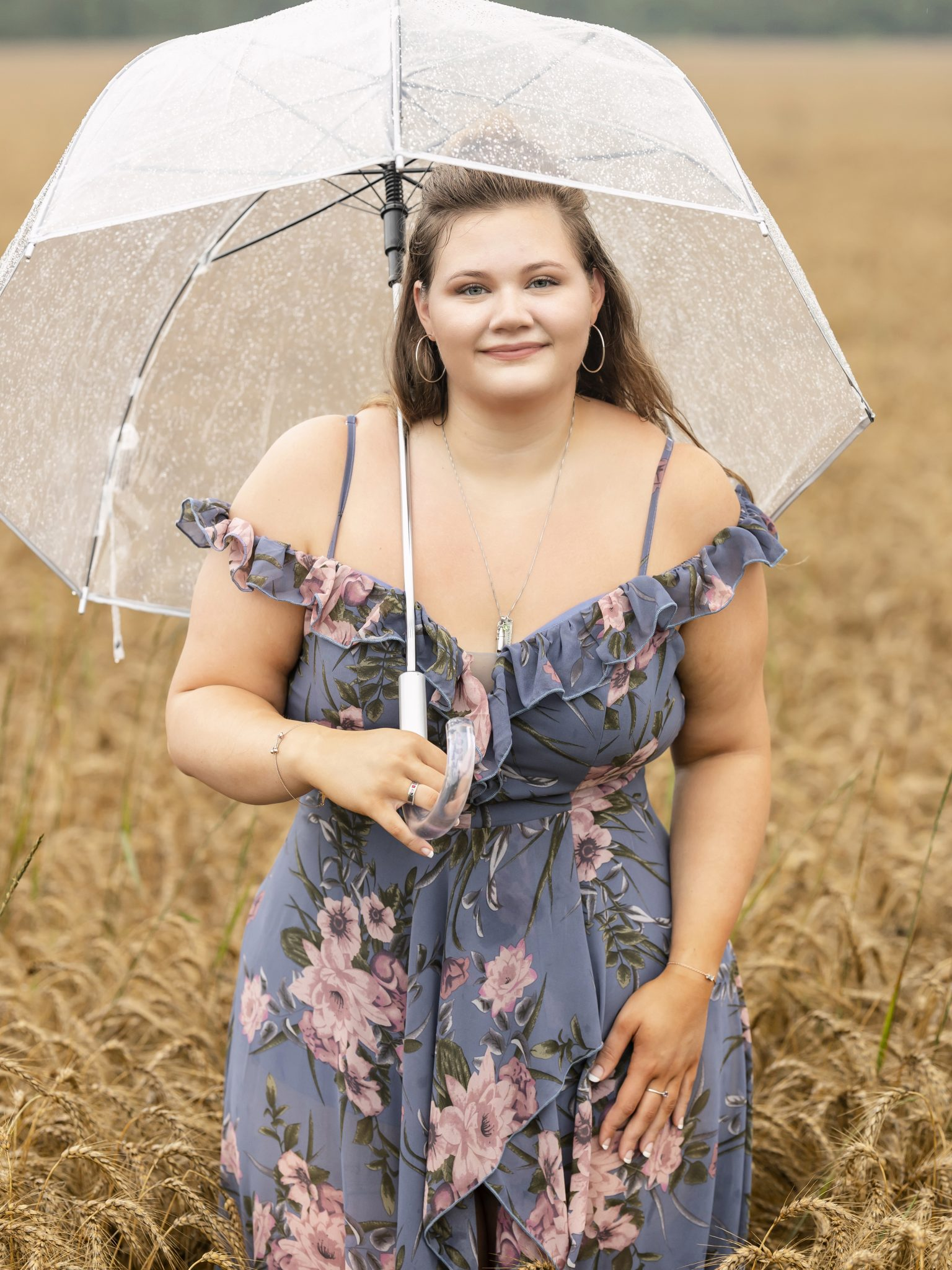 Girl with umbrella standing in a wheat field, long blue floral dress, natural light, portraits, professional portraits, Hilton, NY, Senior Girl pictures, pictures in the rain