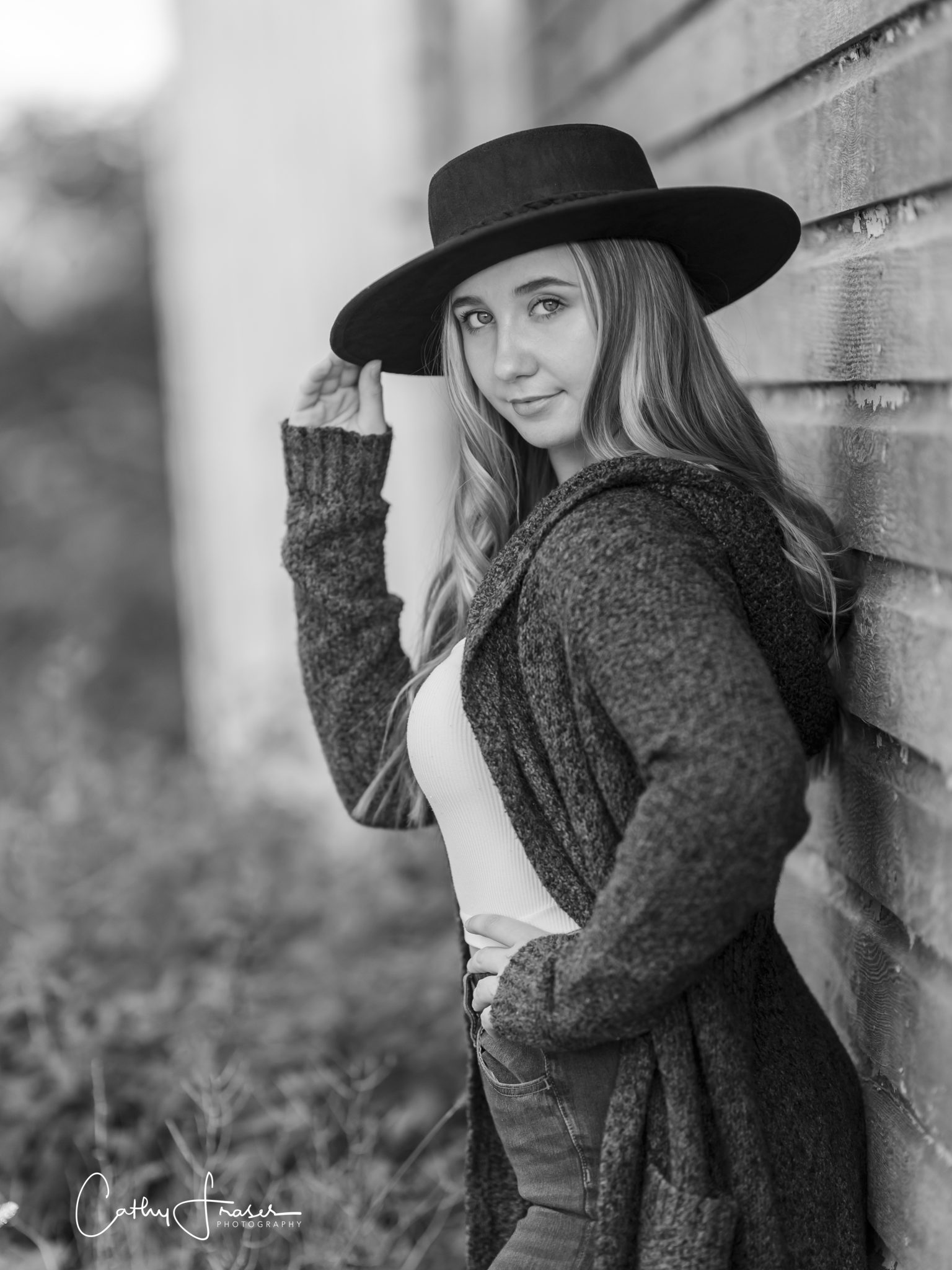 Black & white professional photo, natural light, girl wearing a black wide brimmed hat, sweater , Seneca, New York, girl on fence, leaning on a barn