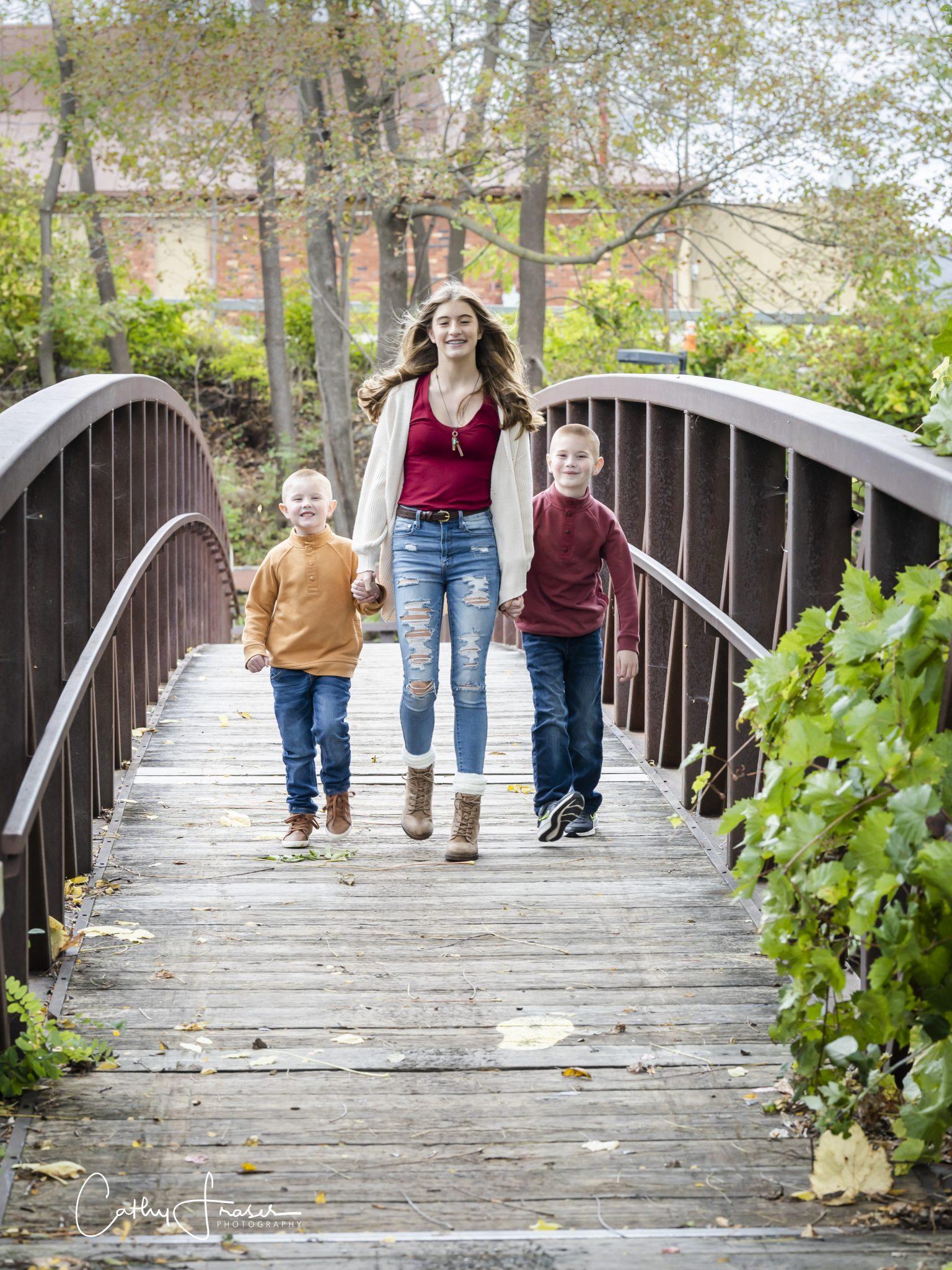 Penn Yan, New York, natural light, siblings walking on footbridge, children in jeans, sweaters