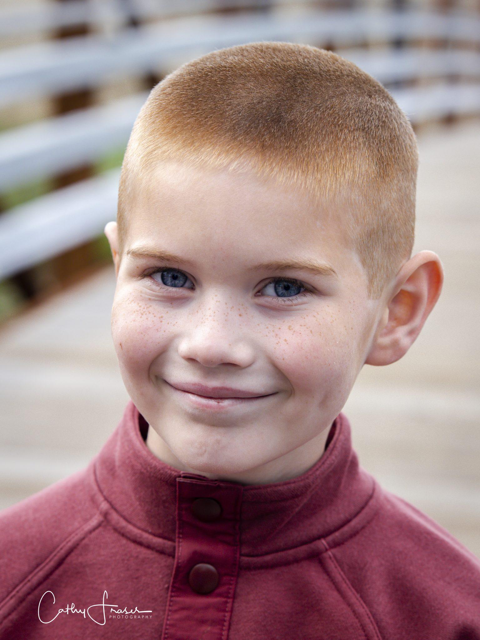 Young boy, professional headshot, Penn Yan, New York, natural light, standing on footbridge wearing red sweater