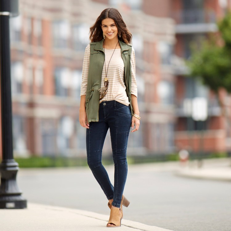 A beautiful woman wearing a neutral striped top, olive green vest and jeans.