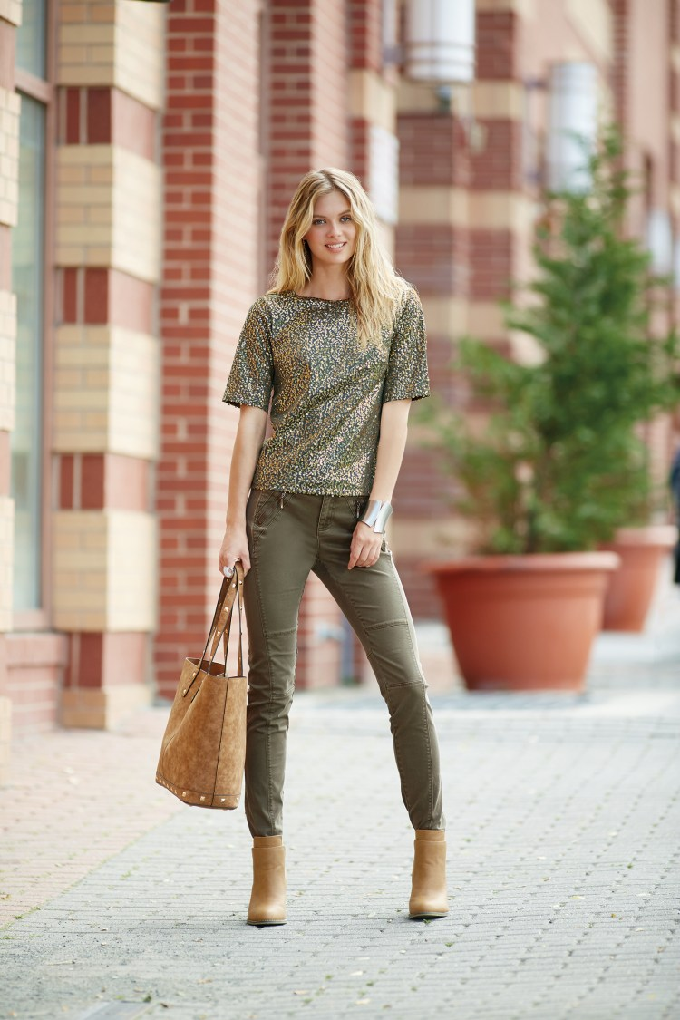 A beautiful woman wearing a sequin top with olive green utilitarian pants.