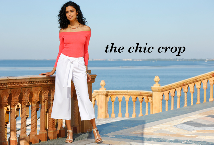 The chic Crop. A beautiful young woman standing outside in an off the shoulder top and white cropped wide leg pants.