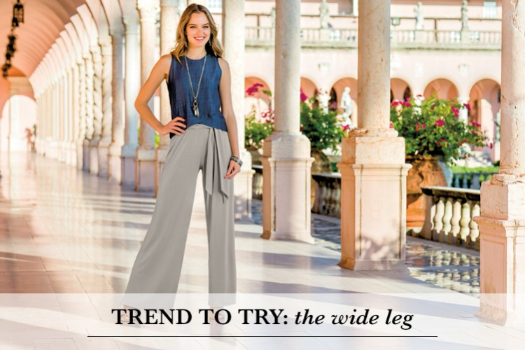 Trend to Try: The Wide Leg. A beautiful young woman is standing outside in a denim sleeveless top and gray wide leg pants.