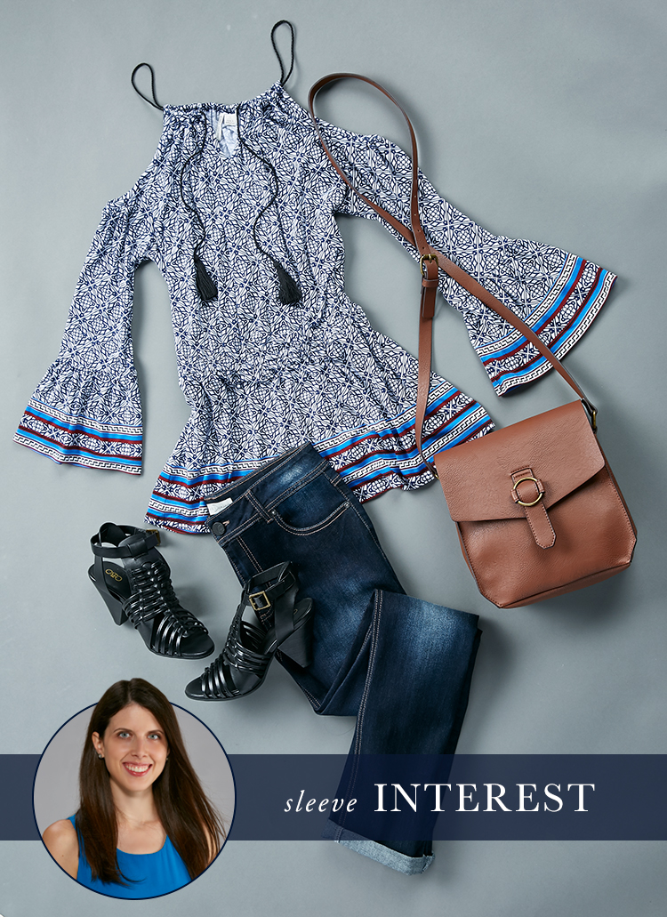 A lay down shot of a cold shoulder flare sleeve top, dark wash jeans, shooties and a handbag.