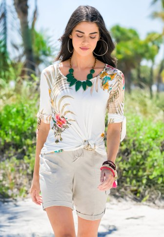 A model walking on the beach in a tropical tie sleeve top with khaki bermuda shorts with earrings, a necklace, and bracelets.
