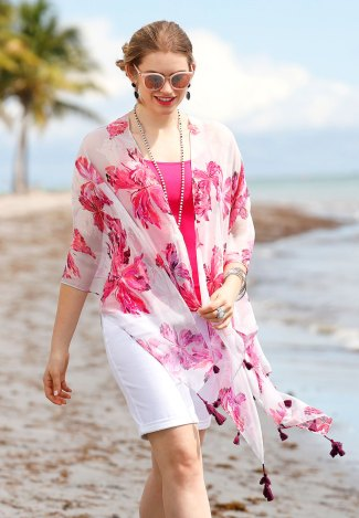 Model walking on the beach in a pretty printed kimono, white bermuda shorts, sunglasses, a necklace and a pink layering tank.