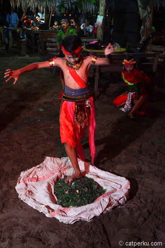 Seorang penari yang masih anak anak beratraksi dengan berjalan diatas pecahan kaca