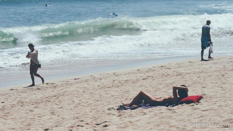Kalau mau cepet ittem, berjemur saja kamu di Pantai Kuta Bali!