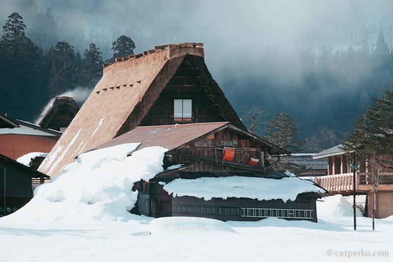 Sisa tumpukan salju masih terlihat, tingginya hampir sama dengan atap rumah.