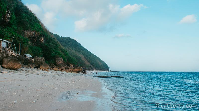 Tebing tinggi menjulang di sisi kiri, menyambung lautan di cakrawala. Inilah yang membuat saya <em>kesengsem</em> dengan Pantai Karma Kandara Beach Club Bali.