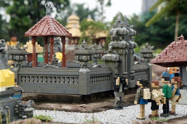 Turis yang lagi foto di depan pura Tanah Lot juga terbuat dari lego