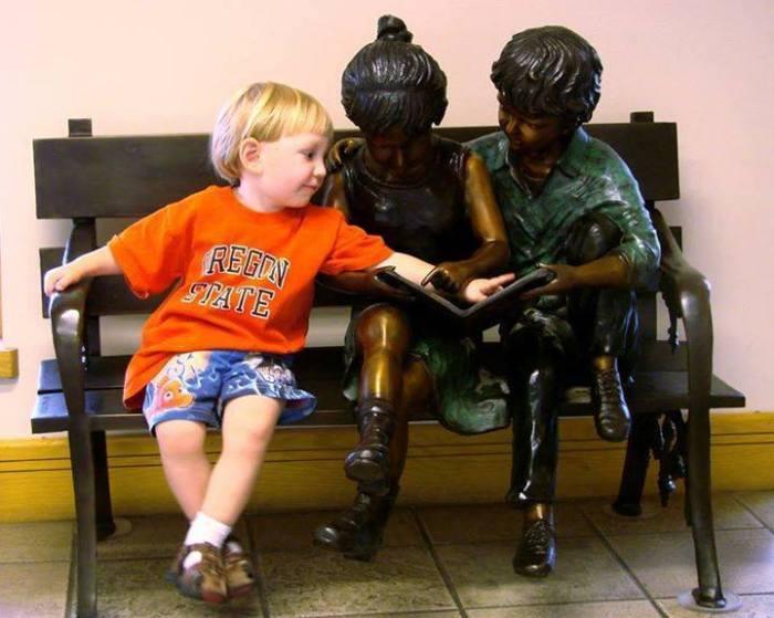 Crianças interagindo com esculturas.