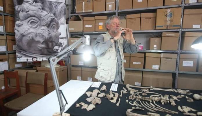 John Rick juntos a los restos humanos encontrados en el lugar.