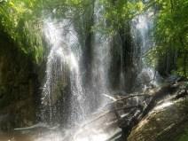 Bottom of Gorman Falls with bright light illuminating spray.