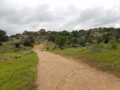 Wide, gravel, Loop Trail with boulders in the distance.