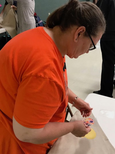 Woman working on a tea towel project during holiday craft workshop.