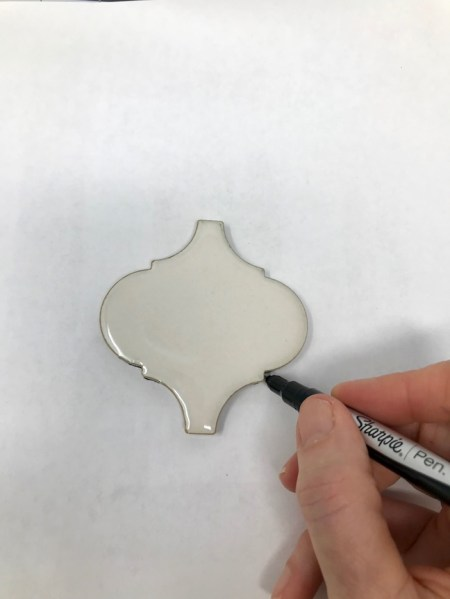 Photo of hand tracing an Arabesque tile