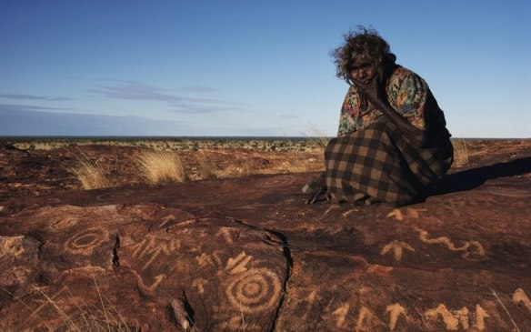 An Aboriginal woman sits by rock carvings in Western Australia. Photograph: Medford Taylor/Getty