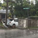 Car smashes into wall, brings down two poles