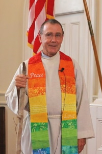 man in white robe with rainbow stole, holding a walking stick