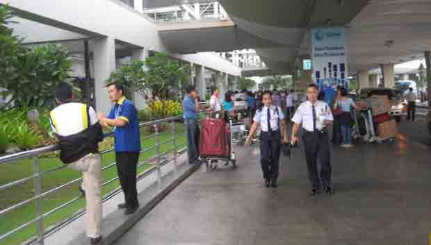 Departing passengers outside Ninoy Aquino International airport terminal