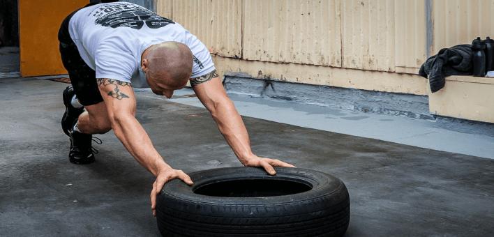un sportif ui s'entraine avec une poussée de pneu