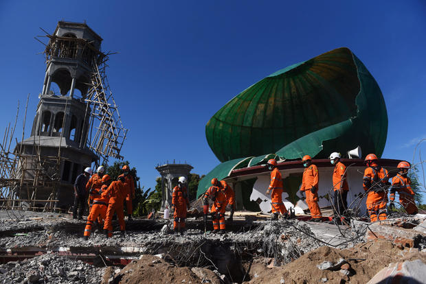 Rescue workers search for victims in a mosque which was damaged in Sunday's earthquake in Tanjung, North Lombok