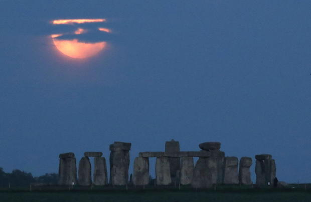 """The full moon known as the """"Super Flower Moon"""" can be seen behind the Stonehenge stone circle near Amesbury"""