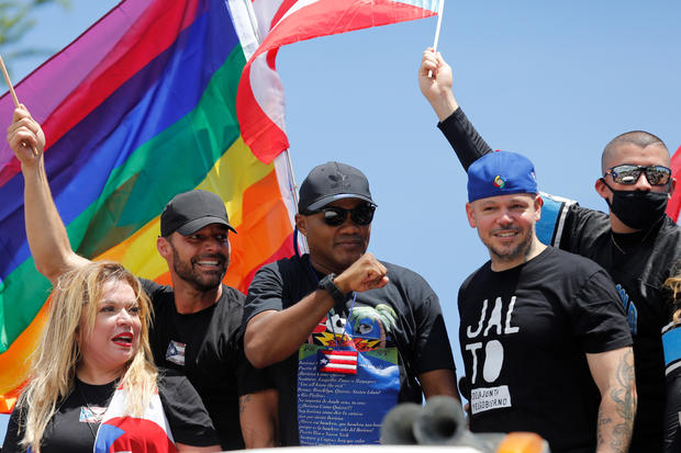 """Puerto Rican boxer Felix """"Tito"""" Trinidad gestures next to his fellow countrymen Residente, Bad Bunny and Ricky Martin during a protest calling for the resignation of Governor Ricardo Rossello in San Juan"""