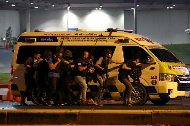 Thailand security forces take cover behind an ambulance as they chase a shooter hidden in a shopping mall after a mass shooting in front of the Terminal 21, in Nakhon Ratchasima, Thailand