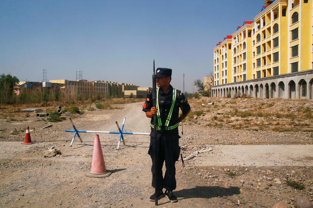 FILE PHOTO: A Chinese police officer takes his position on the road near an official vocational training center in Yining