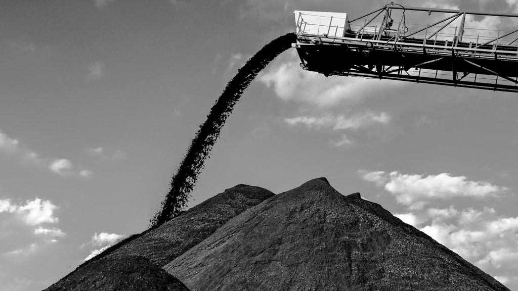Coal being poured onto a huge mound of more coal