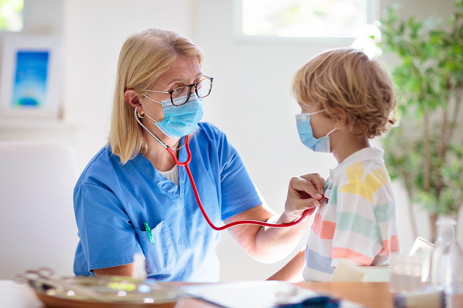 doctor holding stethoscope to child's chest