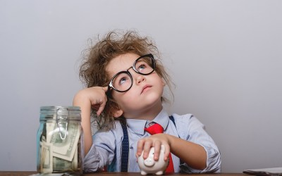 young kid looking up with hand over small piggy bank