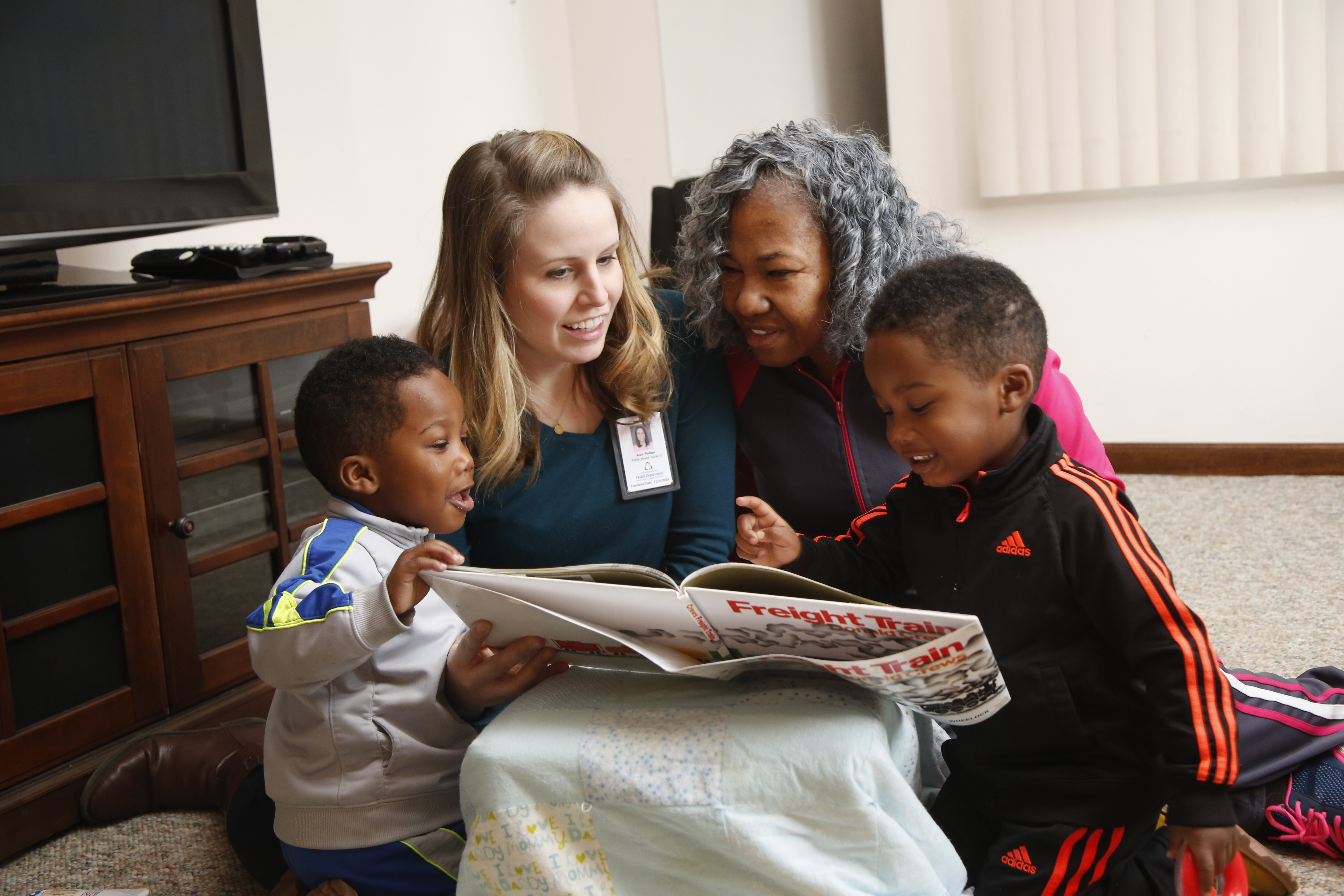 Health Department nurse reading a book with a family