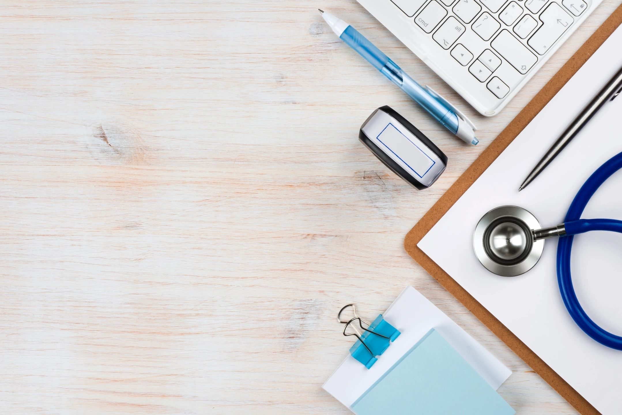Keyboard, mouse, clipboard and stethoscope on a desk