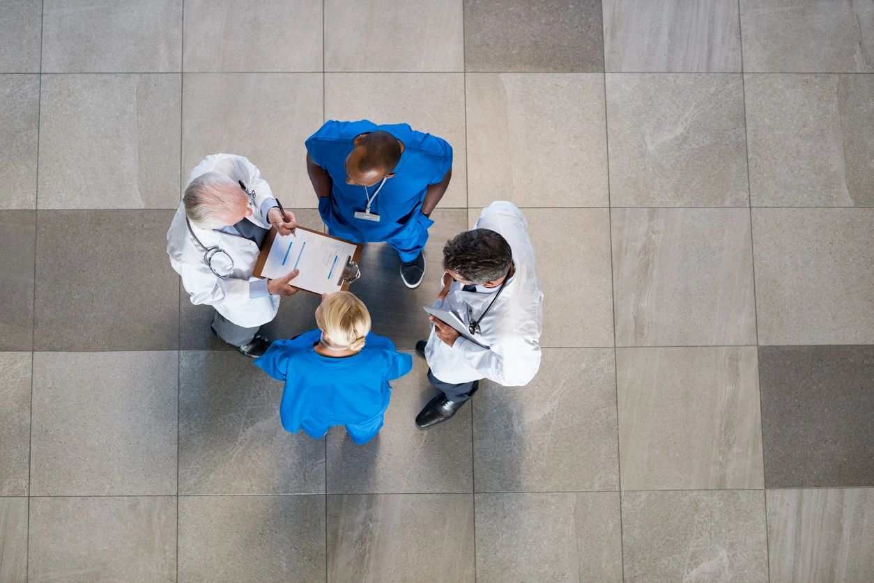 Four doctors talking as seen from above. Two with white coats and 2 in scrubs.