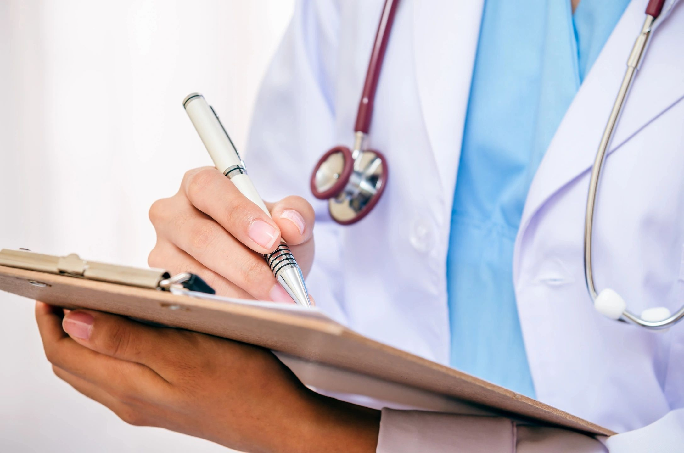 Doctor in white jacket writing on clipboard