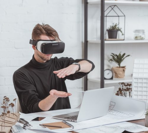 architect in vr headset at workplace with laptop, schemes and building models in office
