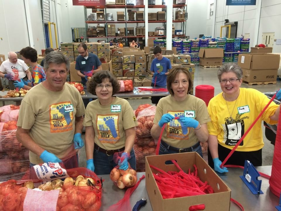 """A church group from West Chicago puts faith into action, working in Northern Illinois Food Bank's processing room. Thanks to volunteers, partners, and donors, a gift of $1 provides $8 worth of groceries to neighbors in need in Northern Illinois."""