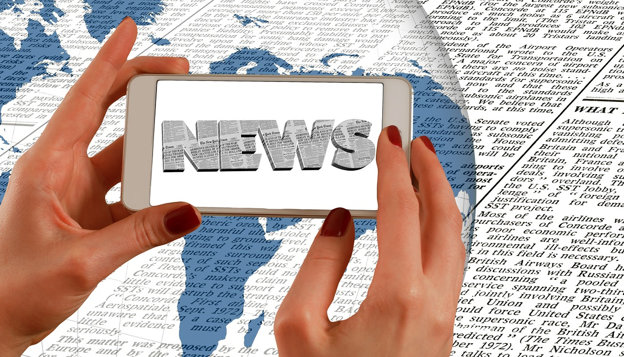 Shot of hands with a Phone and news spelled out in the center over a globe and a newspaper