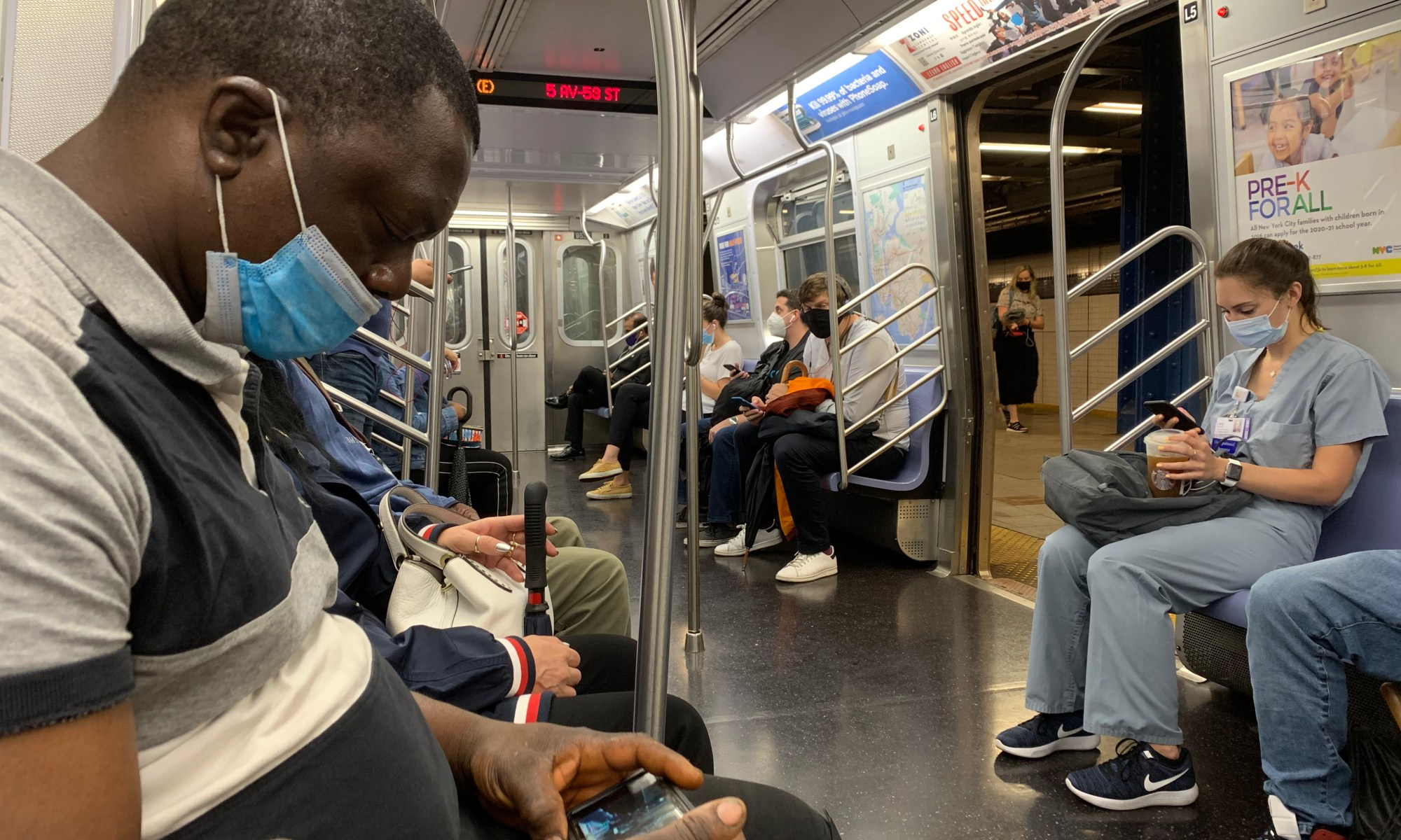 People wearing masks on a NYC subway train. Photo by ConsumerMojo.com