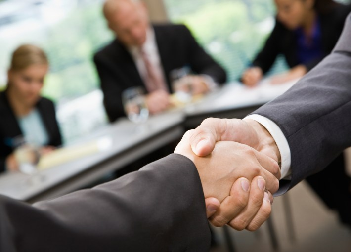 Close up of businessmen shaking hands in conference room