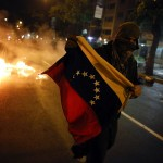 An opposition demonstrator runs with a flag during a protest against Nicolas Maduro's government in Caracas