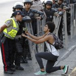 An opposition demonstrator gives flowers to a police officer in Caracas