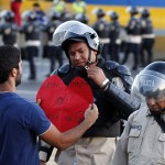 An opposition demonstrator gives a heart-shaped cutting to a police officer in Caracas