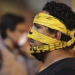 An opposition demonstrator has his face taped during a protest against Nicolas Maduro's government in Caracas