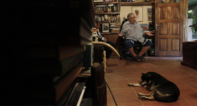 Mujica en su sala exponiendo sus libros y su mascota. Foto Reuters