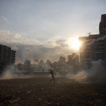 Anti-government protesters stand amidst teargas during a protest at Altamira square in Caracas